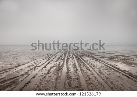 A veil of sea fog lies over the mudflats of the Dee estuary in North Wales at low tide. Vehicle tracks left by fishermen lead to boats stranded in the mud by the receding water.
