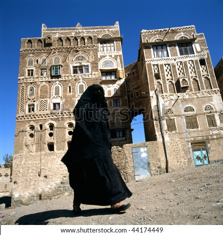 A veiled Muslim woman walks on a Sana a street, Yemen.At background typical Yemen houses.