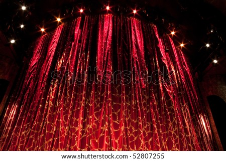 A velvet red theater curtain with traces of gold