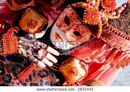 A venetian woman wearing a fancy orange and black costume