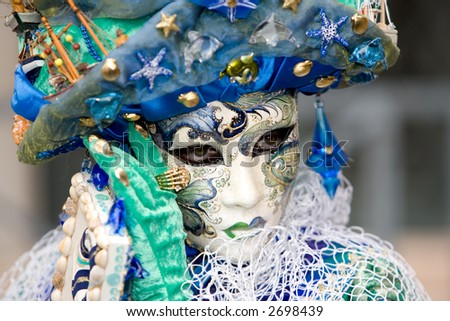 A venetian woman wearing a mask with waves and net over the costume - stock photo