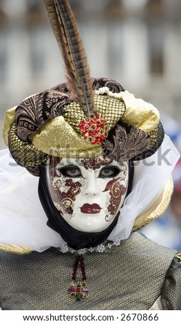 A venetian women in a mask and costume with a pheasant's feather in her hat