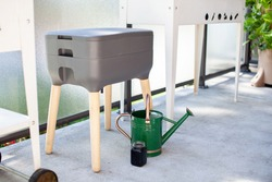A vermicomposting system (worm composter) sits on an apartment balcony with other patio planters. Worms eat food scraps and produce worm castings and worm tea to be used as fertilizer. Redirect waste.