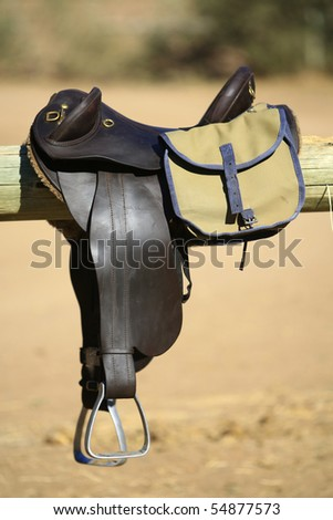 A vertical close up of horse riding gear, including a saddle and bag, in full sunlight