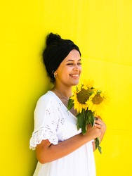 A vertical closeup shot of a young attractive female with sunflowers with yellow wall in the background