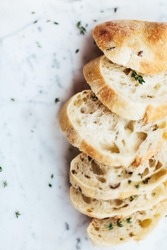 A vertical closeup shot of sliced bread pieces with herbs on a marble white surface