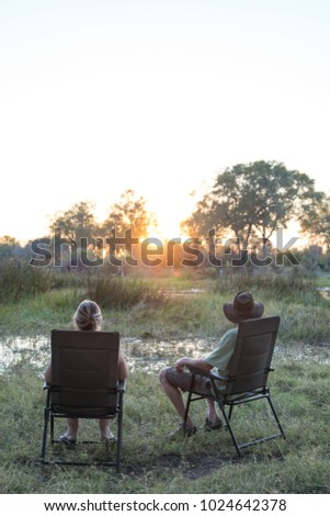A vertical, colour image of a couple sitting in camping chairs at the edge of the water, watching the sun go down in the Okavango Delta, Botswana. #1024642378