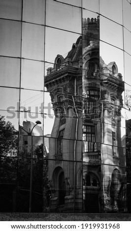 A vertical grayscale shot of a building reflection on a glass building in Bucarest Foto stock ©