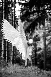 A vertical grayscale shot of a Caucasian blonde girl in angel wings costume with a teddy bear toy