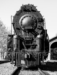 A vertical grayscale shot of an old steam locomotive