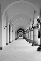 A vertical grayscale shot of arches and columns of a building