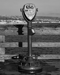 A vertical grayscale shot of sightseeing binoculars on a pier