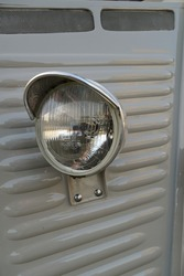 A vertical greyscale shot of a headlight of an old van