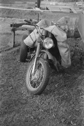 A vertical greyscale shot of a motorcycle on the ground