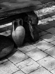 A vertical greyscale shot of an antique water container placed under a wooden table