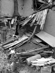 A vertical greyscale shot of the ruins of a building - good for earthquake-related pics
