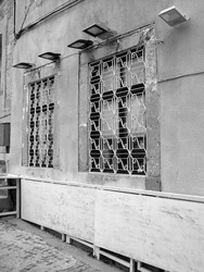 A vertical greyscale shot of the windows of an old building in Izmir behind metal bars