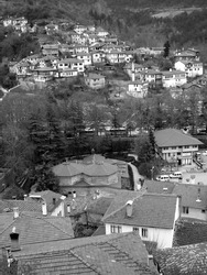 A vertical high angle greyscale shot of a small village on a hill