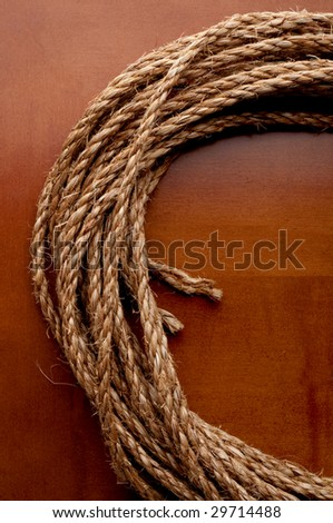 A vertical image of a coil of rope on a wooden surface