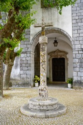 A vertical image of an old cross made from stone standing on the white column in Franciscan Church and Monastery