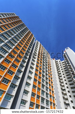 A vertical low angle shot of a new colorful high rise apartment against the sky.