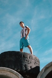 A vertical low angle shot of a young fit confident male posing while standing on a rock