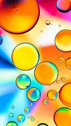 A vertical macro shot of different sized bubbles on a colorful background