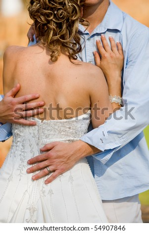 A vertical photo of a caucasian couple holding each other on their wedding day