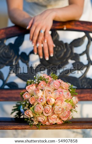 A vertical photo of a rose bouquet resting on a wooden bench, with a caucasian bride leaning behind it