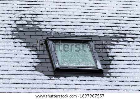 A vertical portrait of a frozen slate roof with a tiltable skylight window which is also frozen during winter time. At the sides of the window the frost has molten because of bad isolation. Foto stock ©