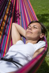 A vertical selective focus shot of a female lying in a rainbow hammock in a sunny day