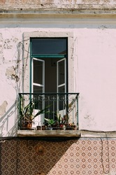 A vertical shot of a balcony with plant vases and half-open glassy doors on a white aged wall