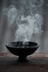 A vertical shot of a burning incense in a black bowl