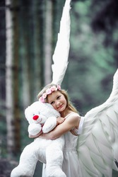 A vertical shot of a Caucasian blonde girl in angel wings costume with a teddy bear toy