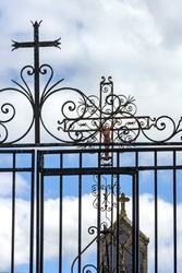 A vertical shot of a cross on the gate at a cemetery