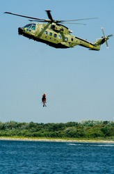 A vertical shot of a diver hanging on a rope of a military helicopter above the river