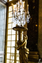 A vertical shot of a golden statue in the Hall of Mirrors in Versailles Palace in France