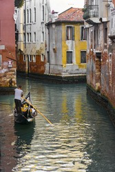 A vertical shot of a gondolier navigating on the canal in Venice surrounded by colorful humble buildings, Italy
