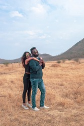 A vertical shot of a happy young Indian couple posing in a field, a traveling couple