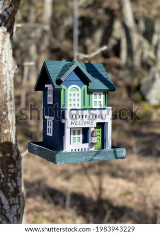 A vertical shot of a house maquette hanging from a tree in a forest on a sunny day Photo stock ©