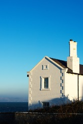 A vertical shot of a house set against the clear blue sky in Anglesey, Wales