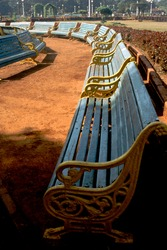 A vertical shot of a line of empty blue sn yellow benches in a park