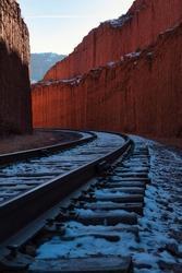 A vertical shot of a long railway through the hills