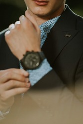A vertical shot of a man fixing cuff-links on sleeve