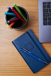 A vertical shot of a pen on a journal, pen box, and laptop on a wooden table