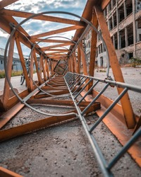 A vertical shot of a rusty crane ladder on a concrete surface