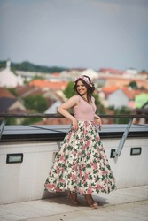 A vertical shot of a smiling caucasian female in a romantic dress with flowers on a terrace