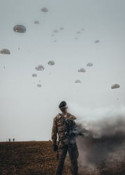 A vertical shot of a soldier in a field on many military parachutists background