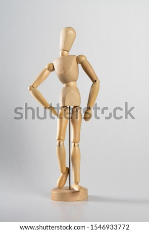 A vertical shot of a wooden pose doll posed like it's walking forward