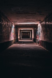 A vertical shot of an old empty underground corridor tunnel of an urban city with graffiti walls